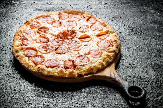 Pizza au pepperoni fraîchement cuit sur table rustique noire.