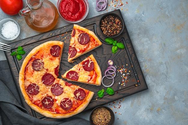 Pizza au pepperoni et ingrédients sur une planche à découper sur fond gris. le concept d'arrière-plans culinaires. vue de dessus, avec espace pour copier.