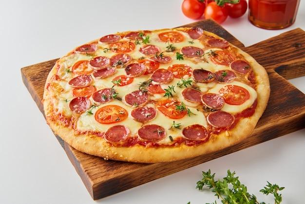 Pizza au pepperoni italien maison chaude avec salami, mozzarella sur table blanche, vue latérale