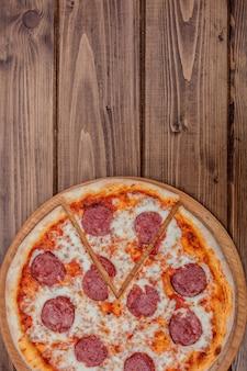 Pizza au pepperoni italienne avec salami sur fond de bois foncé vue de dessus. cuisine traditionnelle italienne. cuisine de rue populaire