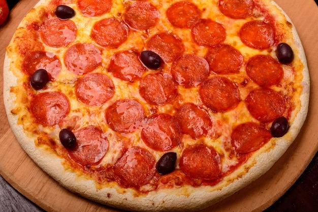 Pizza au pepperoni sur planche de bois et légumes en arrière-plan