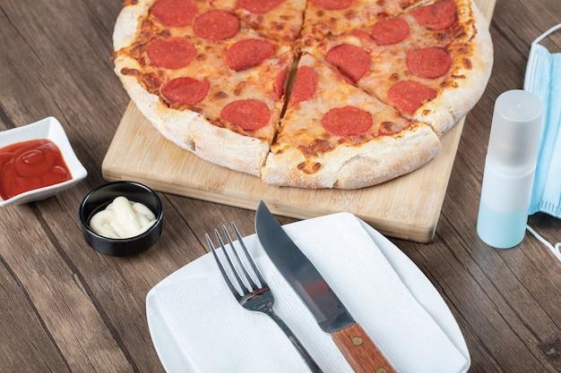 Pizza au pepperoni sur une planche en bois avec sauces, assiette, désinfectant pour les mains et masque autour