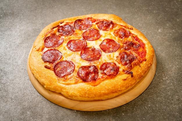 Pizza au pepperoni sur plateau en bois - cuisine italienne
