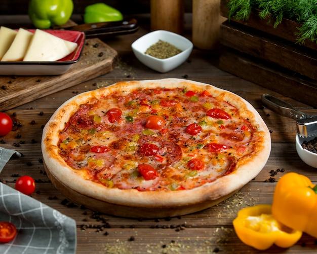 Pizza au pepperoni avec poivrons tomates, herbes et fromage