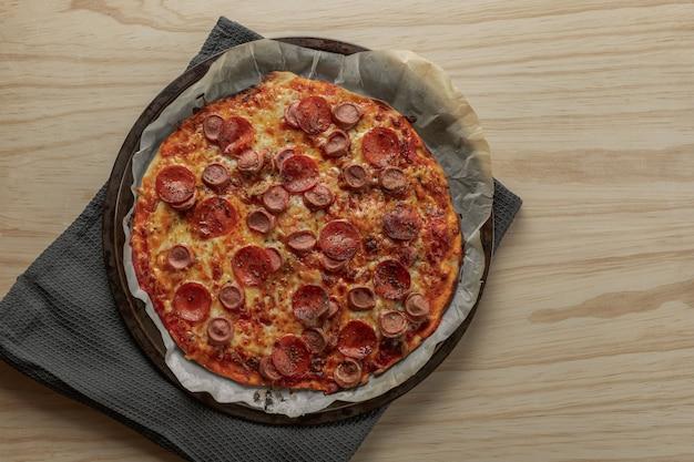 Pizza au pepperoni et saucisse maison sur un plateau en métal avec une serviette noire dans une table en bois