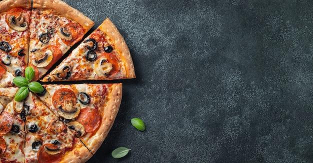 Pizza au pepperoni savoureuse avec des champignons et des olives.