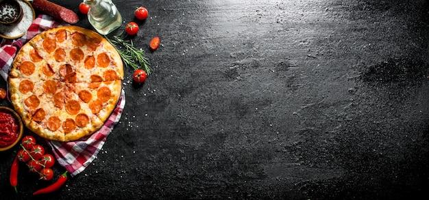 Pizza au pepperoni sur une serviette avec du chili et des tomates. sur fond rustique noir