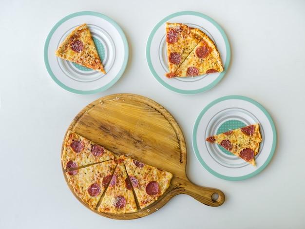 Pizza au pepperoni en tranches sur tableau blanc. vue de dessus.