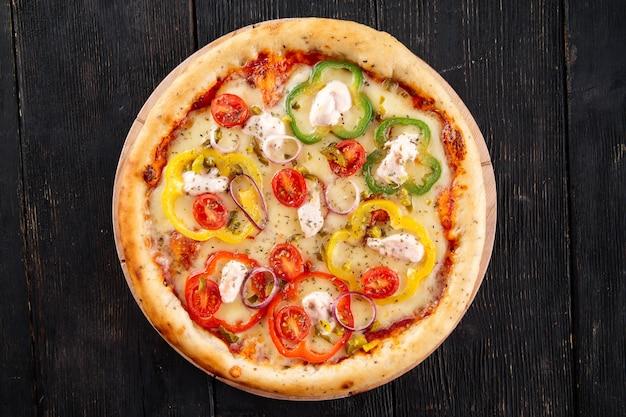 Pizza au poivron et mozzarella sur la table en bois sombre