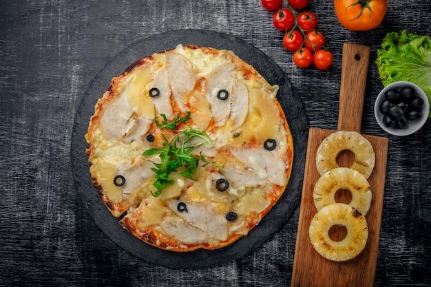 Pizza au poulet, ananas, fromage et olives sur pierre et fond en bois noir griffé