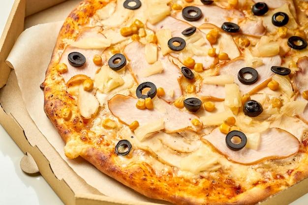 Pizza au poulet et à l'ananas, sauce et fromage fondu, côtés croustillants isolés sur fond blanc