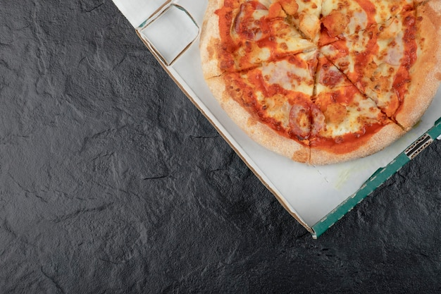 Pizza au poulet buffalo épicé dans une boîte en carton sur une surface noire.
