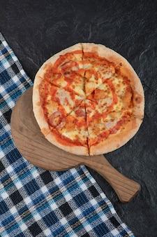 Pizza au poulet buffalo épicé sur planche à découper en bois.