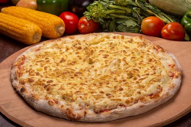 Pizza au poulet et mozzarella sur une planche en bois et légumes en arrière-plan.