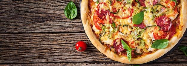 Pizza au poulet, salami, courgettes, tomates et herbes sur table en bois vintage. . bannière. cuisine italienne
