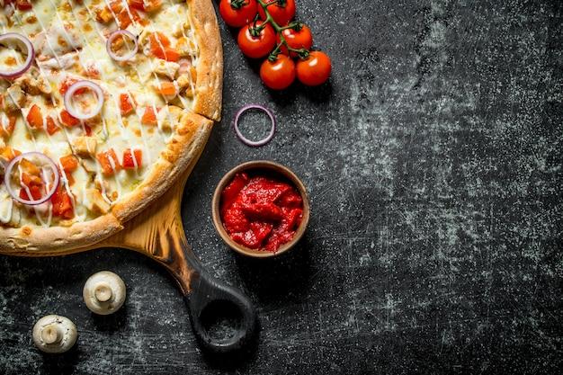 Pizza au poulet et sauce au fromage. sur fond rustique foncé
