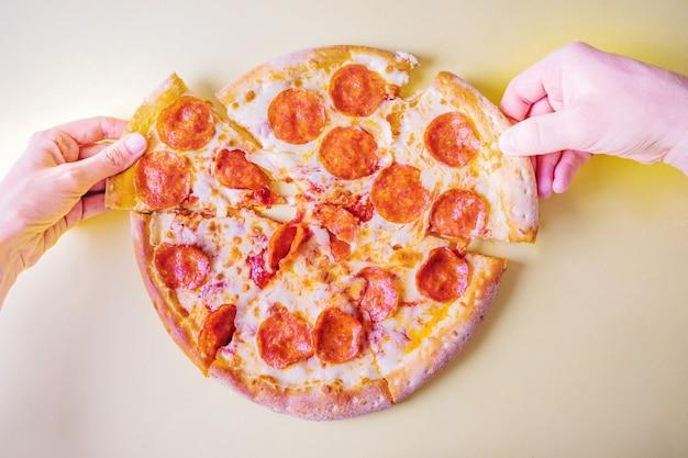 Pizza au poulet et tomates dans une boîte. main prend une part de pizza.