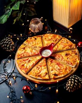 Pizza au poulet en tranches servie avec une sauce au yogourt aux herbes