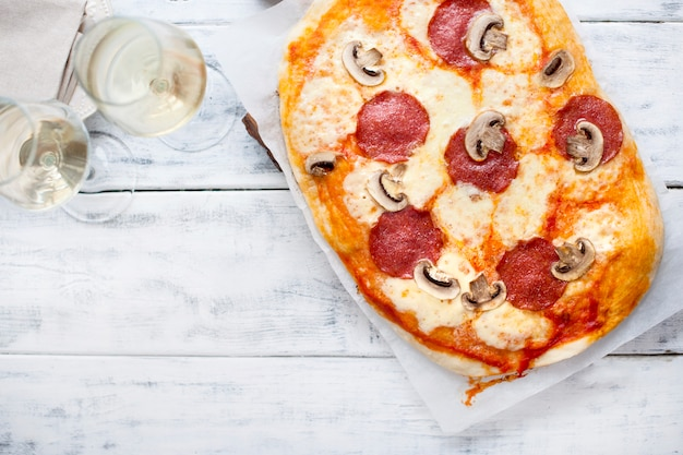 Pizza au salami et champignons sur un fond en bois blanc et deux verres de vin blanc
