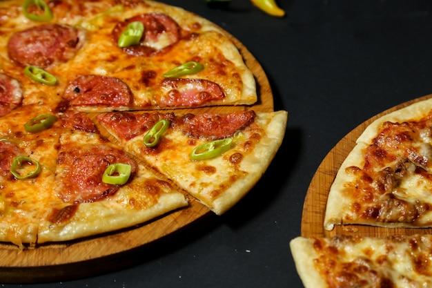 Pizza au salami garnie de tranches de poivron frais vue rapprochée