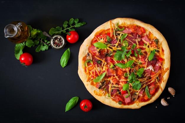 Pizza au salami, jambon, tomate, fromage et champignons. vue de dessus
