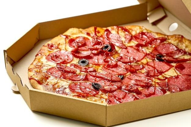 Pizza au salami et saucisses fumées, sauce et fromage fondu, côtés croustillants, isolés sur fond blanc