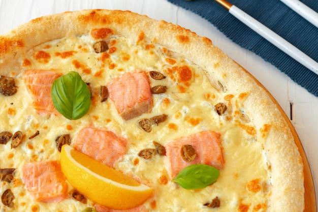 Pizza au saumon cuit sur table en bois
