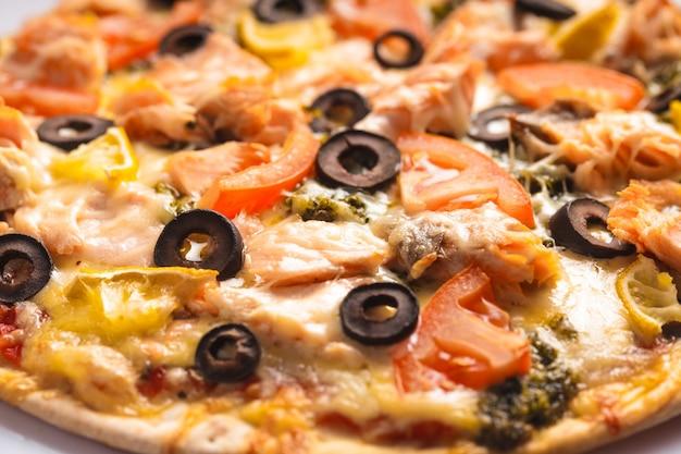 Pizza au saumon, tomates et olives. vue rapprochée