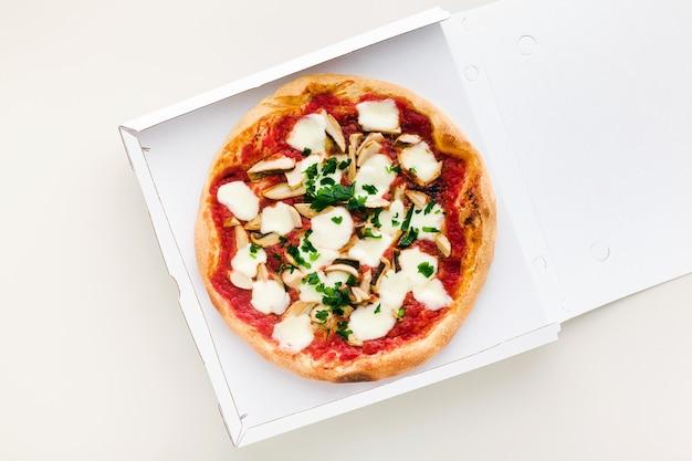 Pizza aux champignons dans une boîte pour livraison, publicité ou menu