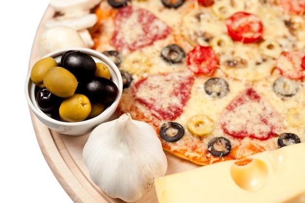 Pizza aux champignons, fromage, saucisses et poivrons. isolé
