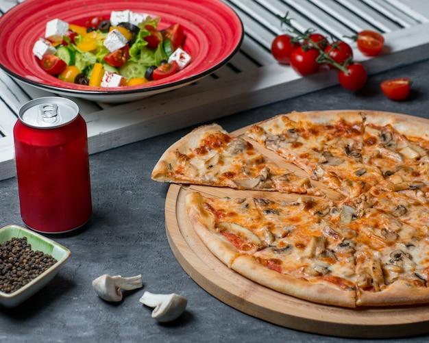 Pizza aux champignons avec salade de légumes et canette de cola