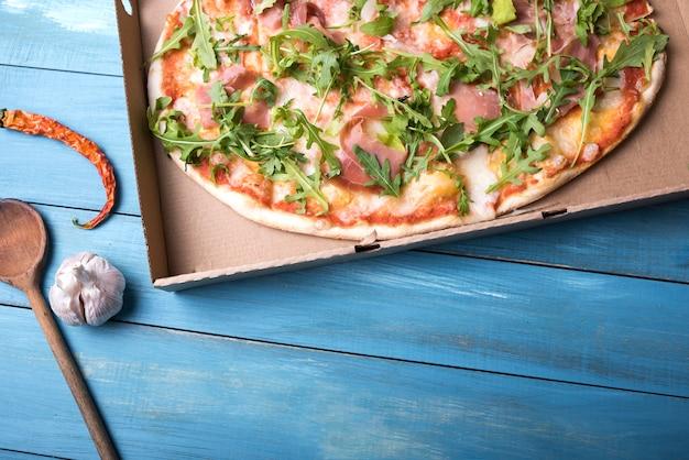 Pizza aux feuilles de bacon et de roquette dans une boîte en carton avec piment rouge et bulbe d'ail sur une table en bois