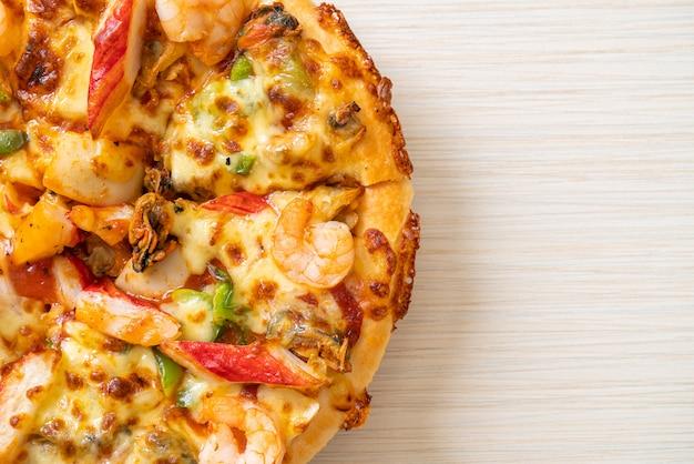 Pizza aux fruits de mer (crevettes, poulpe, moules et crabe) sur plateau en bois