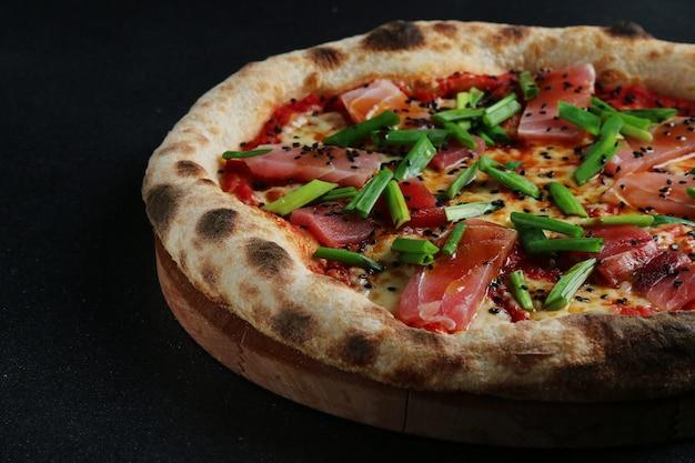 Pizza aux fruits de mer avec du thon frais gros plan sur fond sombre