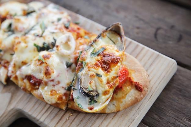 Pizza aux fruits de mer sur fond de bois cuisine italienne