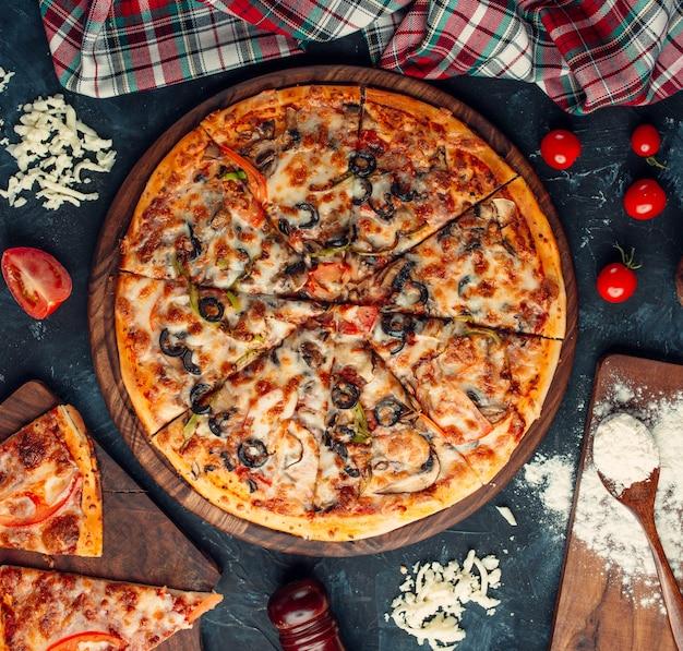 Pizza aux ingrédients mélangés avec du fromage et des tomates.