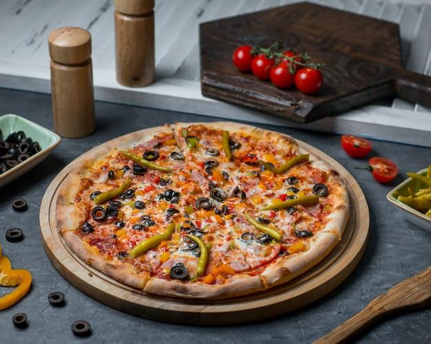 Pizza aux ingrédients mélangés avec piments chili et petits pains aux olives.