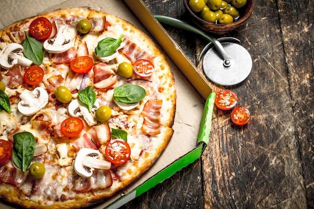 Pizza aux légumes frais dans une boîte.