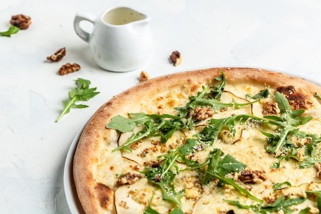 Pizza aux poires avec fromage bleu, noix et roquette. délicieuses pizzas. vue de dessus