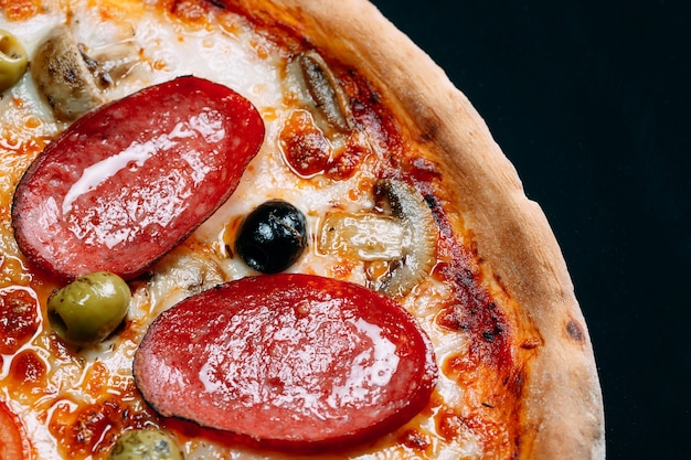 Pizza aux saucisses, champignons, fromage et poivre en gros plan.