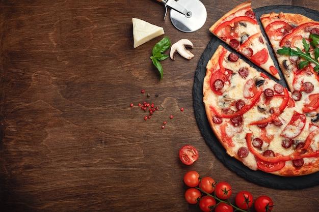 Pizza aux saucisses fumées, fromage, champignons, tomates, poivrons sur une pierre et un plateau en bois brun.
