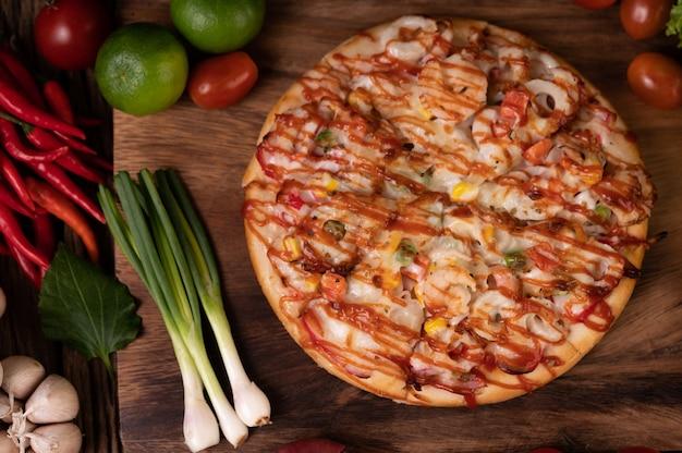 Pizza aux saucisses, maïs, haricots, crevettes et bacon sur une assiette en bois