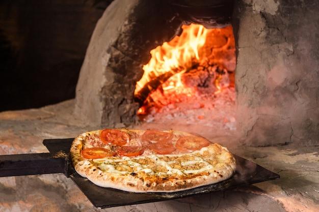 Pizza aux tomates et aux quatre fromages fraîchement sortie d'un four artisanal paraguayen (tatakua).