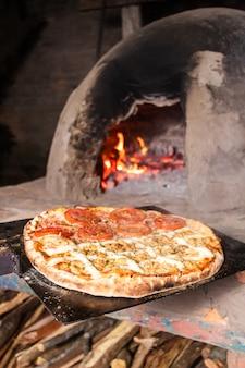 Pizza aux tomates et aux quatre fromages fraîchement sortie d'un four paraguayen en ciment (tatakua).