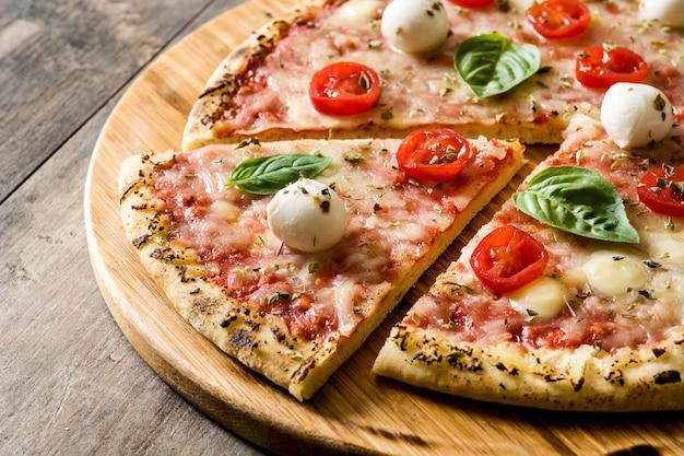 Pizza aux tomates, fromage et basilic sur table en bois