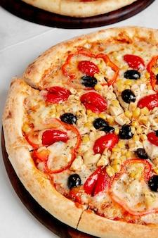 Pizza aux tomates olives poivrons et maïs