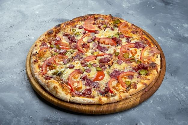 Pizza aux tomates, saucisses et fromage sur fond gris