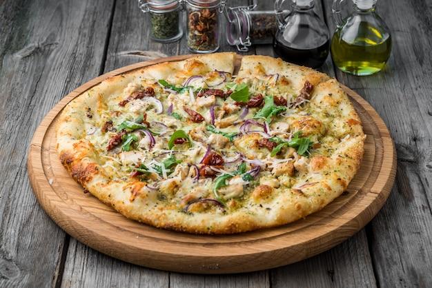Pizza aux tomates séchées au soleil, prosciutto, roquette et parmesan