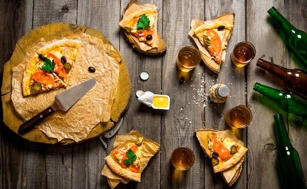 Pizza et bière pour quatre personnes sur une table en bois.