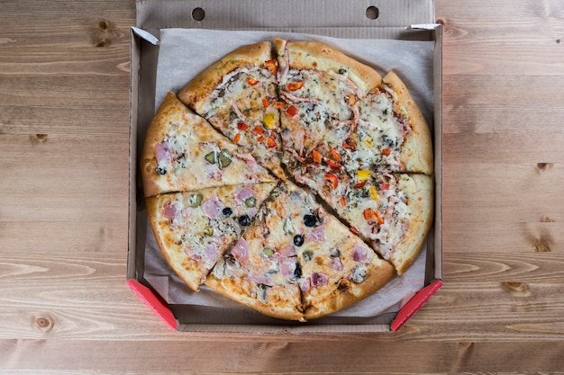 Pizza en boîte ouverte sur une table en bois, livraison de restauration rapide